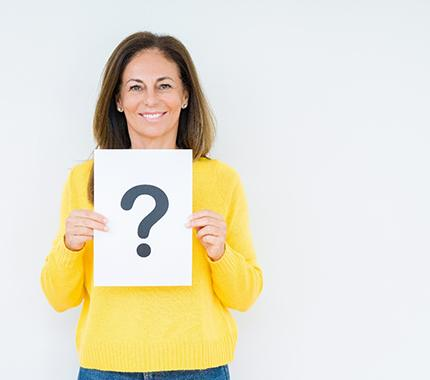 Smiling woman with questions about dental implant procedure