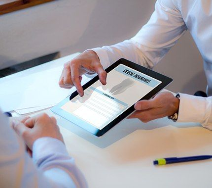 Team member showing patient dental insurance forms on tablet computer