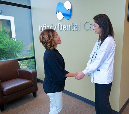 Dr. Kalluri shaking hands with dental patient