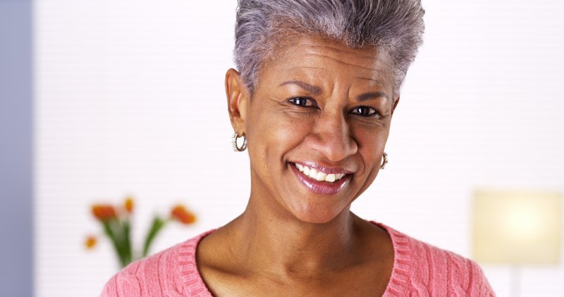 older woman smiling happily after receiving dental implants